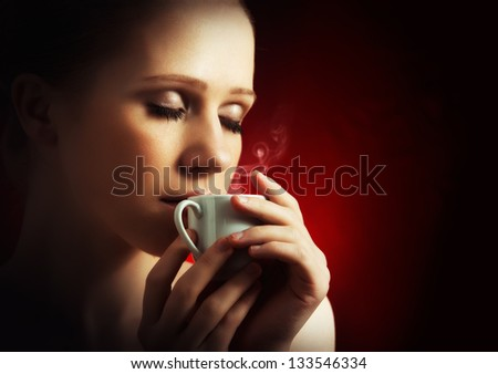 portrait of sexy woman enjoying a hot cup of coffee on a dark background - stock photo
