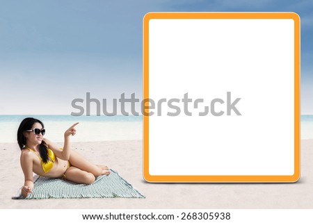 Portrait of sexy woman in bikini pointing at copyspace - stock photo
