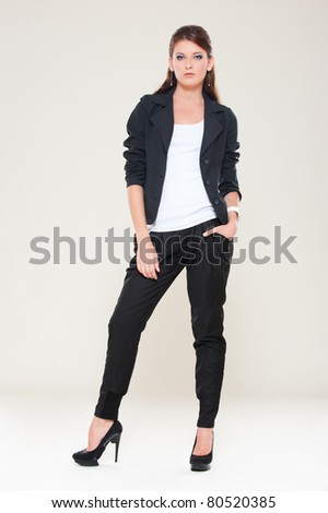 portrait of sexy woman in black jacket posing over grey background - stock photo