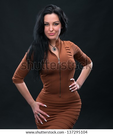 Portrait of sexy woman in brown dress on a gray background - stock photo