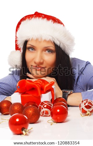 Portrait of sexy woman posing in studio in christmas hat with presents