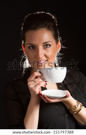 Portrait of sexy woman posing on black background with cup of coffee