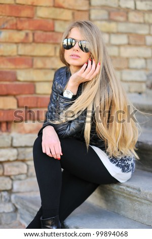 Portrait of sexy woman sitting on the stairs in sunglasses - stock photo