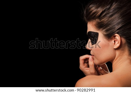 Portrait of sexy woman with black party mask on face, isolated on black - stock photo