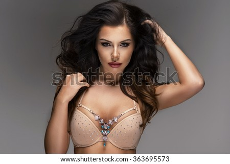 Portrait of sexy woman with long curly hair. Studio shot.