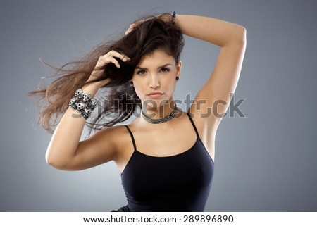Portrait of sexy woman with windtorn long hair, looking at camera with hands in hair. - stock photo