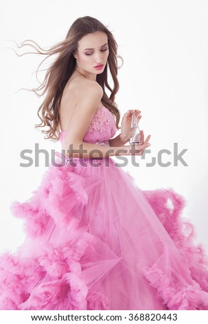 Portrait of sexy young beautiful caucasian blonde in gorgeous pink dress on white background