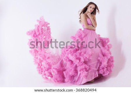 Portrait of sexy young beautiful caucasian blonde in gorgeous pink dress on white background - stock photo