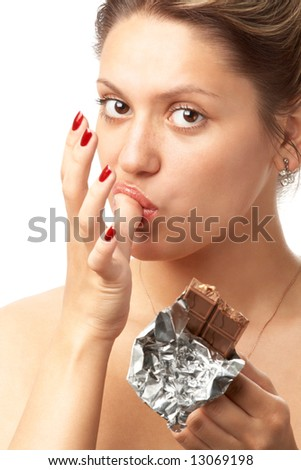 portrait of sexy young girl licking her thumb with bar of chocolate; isolated on white