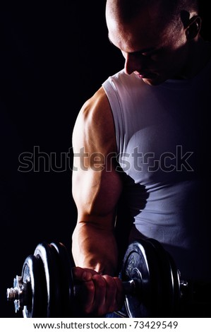 Portrait of sexy young man showing his muscular arm - stock photo