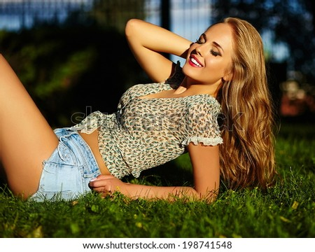 portrait of sexy young stylish smiling woman girl model in bright modern cloth with perfect sunbathed body outdoors lying on green grass in the park in jean shorts holding healthy strong hair in hand - stock photo