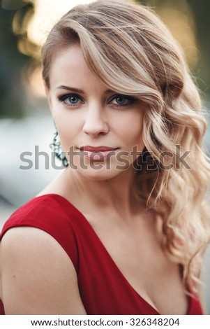 portrait of sexy  young woman in red dress with long blond hair, beautiful eyes, sensual lips and clean skin, beautiful hair, piercing eyes straight stranded hair hair, curly hair, earrings jewelry - stock photo