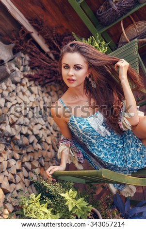 Portrait of sexy young woman sitting on a wooden chair in the garden