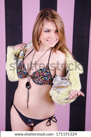 portrait of sexy young woman wearing underwear and fur coat - stock photo