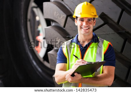 portrait of shipping company employee standing in front of industrial tires