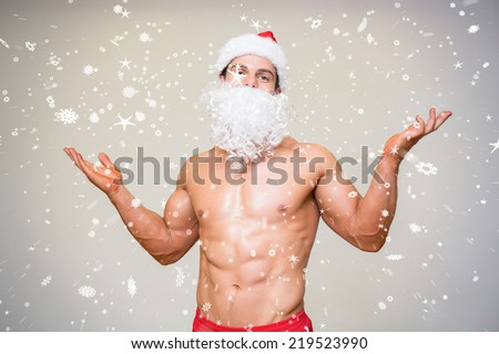 Portrait of shirtless macho man with fake santa beard against snow falling - stock photo