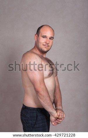 Portrait of shirtless man posing and showing his triceps and strong body.