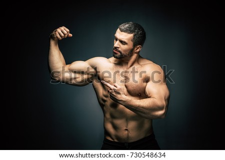 portrait of shirtless sportive man  pointing at biceps isolated on black