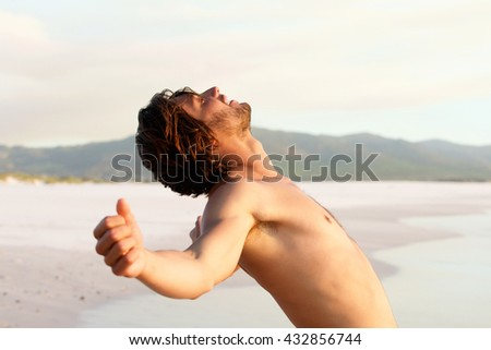 Portrait of shirtless young man leaning back by beach - stock photo