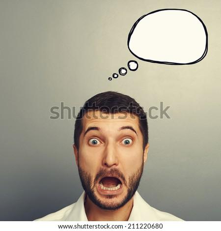 portrait of shocked businessman with empty speech bubble over dark background - stock photo