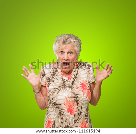 Portrait Of Shocked Elderly Woman Isolated Over Green Background - stock photo