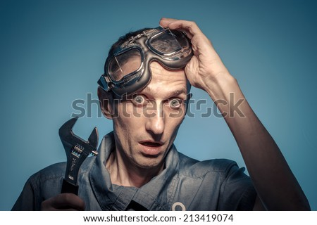 Portrait of shocked locksmith with the adjustable wrench. - stock photo