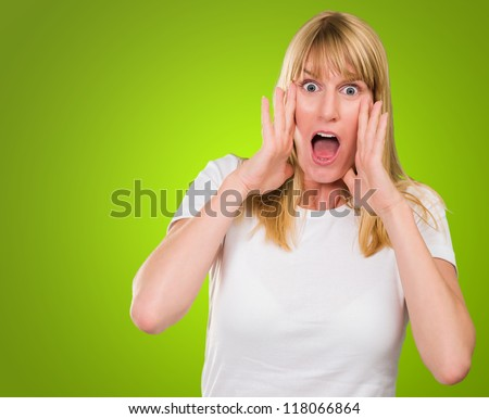 Portrait Of Shocked Woman against a green background - stock photo