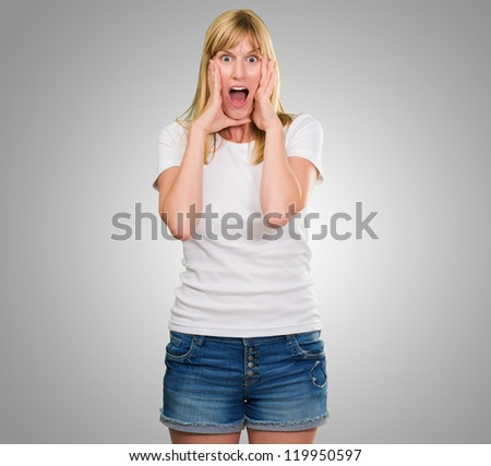 Portrait Of Shocked Woman against a grey background