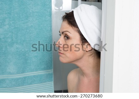 Portrait of shocked woman covering her body with towel - stock photo