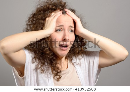 portrait of shocked young woman over grey background - stock photo