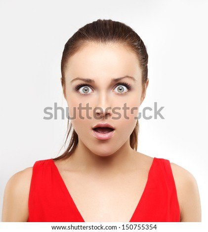 Portrait of shocked young woman staring at the camera - stock photo
