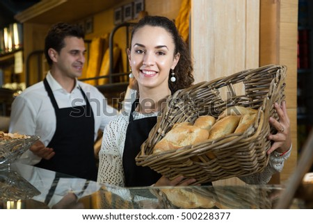 Portrait of shop assistant woman with basket of loaves and guy in backgroung offering tasty baguettes in bakery