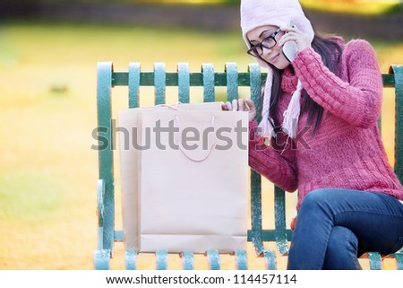Portrait of shopping woman sitting on the bench with bags and talking on the phone. shot outdoor - stock photo