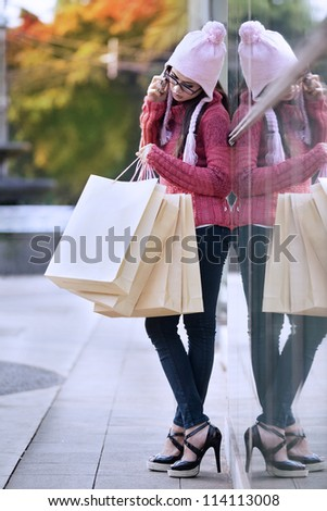 Portrait of shopping woman with bags talking on the phone. shot outdoor - stock photo