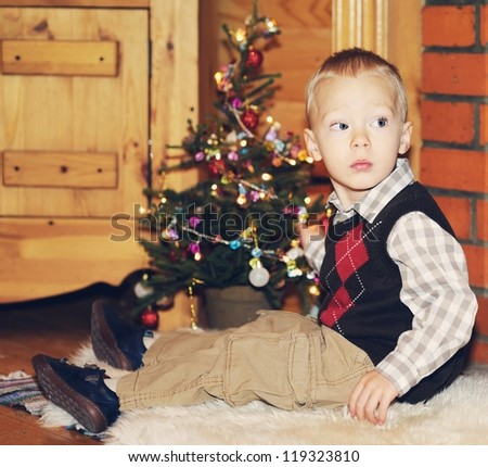 Portrait of short-haired toddler boy in Christmas decorations