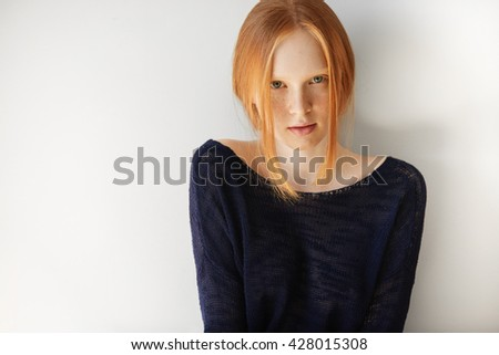 Portrait of shy and thoughtful teenage female looking and smiling at the camera. Pretty redhead student girl in casual top relaxing indoor after classes at school. People and lifestyle concept - stock photo
