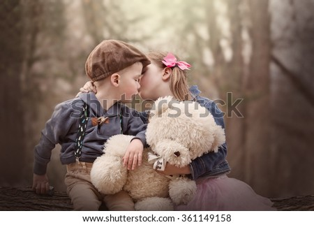 portrait of siblings sitting together outside holding a teddy bear and kissing - stock photo