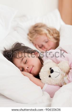 Portrait of siblings sleeping in a bedroom - stock photo