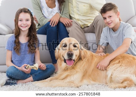Portrait of siblings with dog and parents sitting behind at home - stock photo
