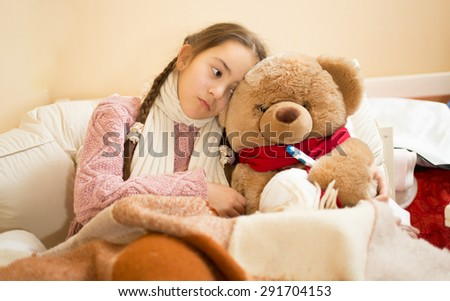 Portrait of sick girl resting in bed with brown teddy bear