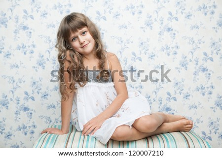 Portrait of sincere cheerful tender young blond girl child with grey eyes and wavy long hair in relaxed sitting posture looking at camera - stock photo