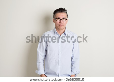 Portrait of single mature 50s Asian man in casual business standing over plain background with shadow. - stock photo