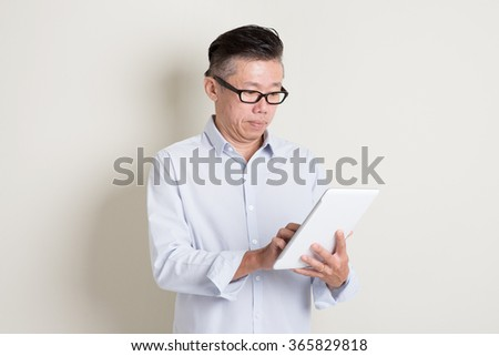 Portrait of single mature 50s Asian man in casual business using digital tablet computer, standing over plain background with shadow. Chinese senior male people. - stock photo