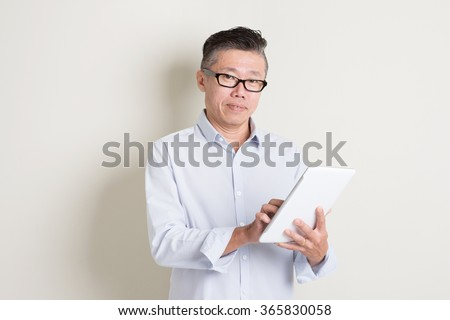 Portrait of single mature 50s Asian man in casual business using digital tablet pc, standing over plain background with shadow. Chinese senior male people.