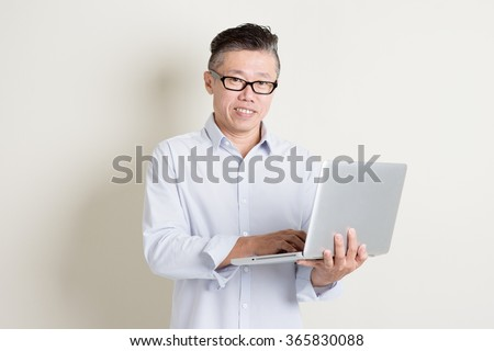 Portrait of single mature 50s Asian man in casual business using laptop pc and smiling, standing over plain background with shadow. Chinese senior male people.