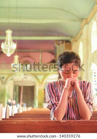 Portrait of single young girl praying in the  Baclayon Church, Bohol, Philippines, one of the oldest and best preserved churches in the Philippines, also known as one of the local landmarks