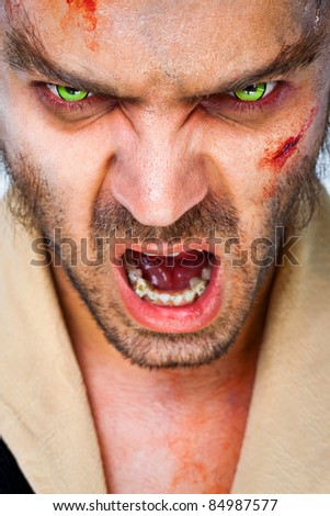 Portrait of sinister man wolf with scary green artificial eyes, mouth open - stock photo