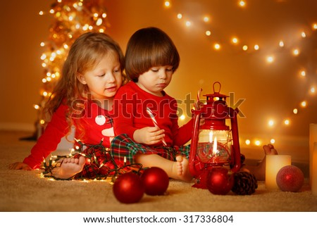 Portrait of sister and brother playing at Christmas evening with lantern and light.  - stock photo