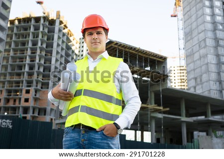 Portrait of site manager posing with blueprints against unfinished building - stock photo