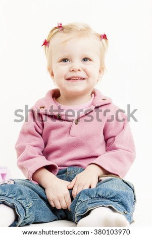portrait of sitting little girl wearing jeans